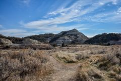 A path leads across the grassland canyons. stock photo