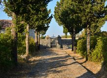 Path and a church gate. Path that leads to a church entrance with an open gate Royalty Free Stock Photography
