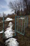 A path with melting snow passing through the gate and running away into the distance stock photo
