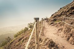 Path on Mount Vesuvius crater and view over Naples Bay on a foggy day. Path on Mount Vesuvius crater with the protection rope along the hiking trail and a view stock image
