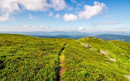 Path through the mountain ridge in summer. Summer mountain landscape. footpath down the hill through mountain ridge to valley. huge boulders on grassy slope Royalty Free Stock Photo