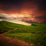 Path through a mystery mountain meadow to horizon. Parth through a mystery mountain meadow to horizon with sunset clouds Stock Photo