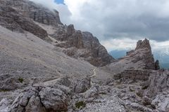 Path near giant boulders in a dark and cloudy mountain scenery. Dolomites, Cortina d`Ampezzo, Italy royalty free stock image