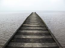Path into nowhere. A wooden path leading into endless waters Stock Images