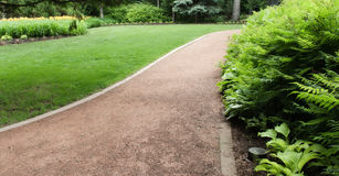 Path In The Park. A groomed path running through a park with bushes on the right side of the image Stock Photography