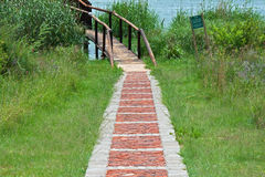 PATH PAVED WITH BRICKS WITH WOODEN BRIDGE Stock Image