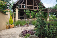 Path with perennials. A pebble pathway winds past a custom-designed backyard patio shelter Stock Photos