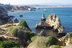 Path on sandstone rock formations around Lagos, Portugal. With view of long sand stretch of Meia beach Royalty Free Stock Photo
