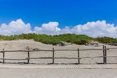 Path on sandy beach under blue sky stock photo