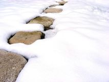 Path in the snow. Path of large flat stones on the snow on a sunny day Royalty Free Stock Image