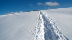Path in snow leading to the top. Narrow path in fresh snow, leading to the top of the Slivnica mountain near Cerknica, Slovenia Royalty Free Stock Photo