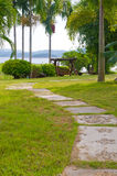Path of stepping stones leading into lush green g Stock Photos