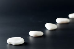 Path of stones. Path of white stones over black background Royalty Free Stock Image
