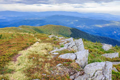 Path on a stony high ridge. Path in the grass near rugged stones on a high ridge Royalty Free Stock Photos