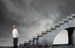 Path of studies. Child standing in front of a stairway Stock Image