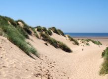 Free Path Through Tall Grass Covered Sand Dunes Leading To A Beach And Bright Blue Sea In Summer Sunlight On The Sefton Coast Royalty Free Stock Photo - 153013835