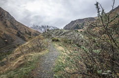 Path to ancient medieval monument in mountains of Caucasus. Christian cross in touristic place.  Royalty Free Stock Photos