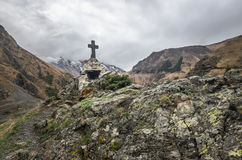 Path to ancient medieval monument in mountains of Caucasus. Christian cross in touristic place.  Stock Photography