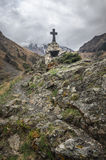 Path to ancient medieval monument in mountains of Caucasus. Christian cross in touristic place.  Royalty Free Stock Photography