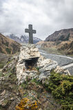 Path to ancient medieval monument in mountains of Caucasus. Christian cross in touristic place.  Royalty Free Stock Images
