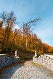 Path from the in to the autumn forest. Path from the stone bridge in to the forest. trees in fall colors. blue sky above the landscape royalty free stock photo