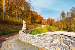 Path from the in to the autumn forest. Path from the stone bridge in to the forest. trees in fall colors. blue sky above the landscape stock photography