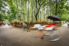 Path to bamboo forest with blurred tourists in Arashiyama, Kyoto. Wide angle long exposure in Arashiyama bamboo forest with blurred tourists, Kyoto, Japan Stock Images