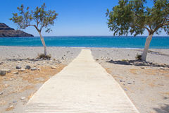 Path to the beach with blue transparent water Royalty Free Stock Images
