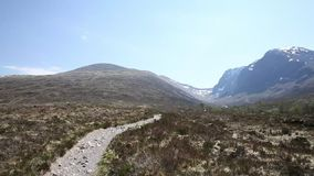 Path to Ben Nevis Scotland UK with snow topped mountains in the Grampians Lochaber Highlands pan stock footage