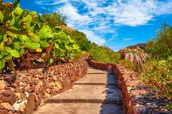 Path to the castle of Malaspina above the village of Bosa on a sunny day - Sardinia. Ancient, antique, architecture, bricks, buildings, cross, effect, facade royalty free stock image