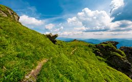 Path to the edge of a hill. Beautiful mountainous landscape with grassy hillside and giant boulders under. fine weather with blue sky and some clouds Stock Photography