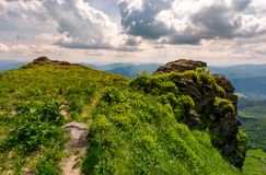 Path to the edge of a rocky cliff. Beautiful landscape of Carpathian mountains on a cloudy summer day Stock Image