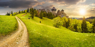 Path to fortress ruins on hillside with forest at sunset. Composite mountain landscape. curve path to abandoned ruins of ancient fortress through green meadow on Stock Photo