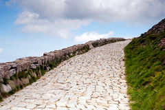 Path to heaven. Stone path leading to the sky. Stone wall at the left Stock Photo