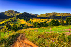Path to highland. The road to the high mountains in the early morning near the wooden fence Stock Photo