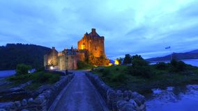 Path to illuminated Eilean Donan Castle over the lake in Scotland, UK stock footage