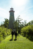 Path to lighthouse. A lighthouse in toronto center island with silhouettes walking towards it Royalty Free Stock Images