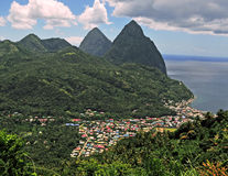 Path to the Piton Mountain Range. A view of a coastal island town in the valley below a mountain range Royalty Free Stock Photos