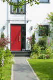 Path to the red Frontdoor. Red frontdoor with blooming plants beside the path to house entrance Stock Photo