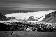 Path to Skaftafellsjokull glacier with few unrecognisable people. In Skaftafell, Iceland in summer, black and white with grain Royalty Free Stock Photos
