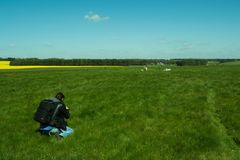 Photographer taking photos of the landscape. The path to Stonehenge - UNESCO World Heritage Site. Prehistoric monument that consists of a ring of standing Royalty Free Stock Photography