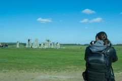Photographer taking photos of the landscape. The path to Stonehenge - UNESCO World Heritage Site. Prehistoric monument that consists of a ring of standing Stock Image