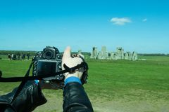 Photographer taking photos of the landscape. The path to Stonehenge - UNESCO World Heritage Site. Prehistoric monument that consists of a ring of standing Stock Photos