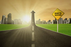 The path to success. Guidepost with showing the road to success turning into arrow upward with bright sunrise Royalty Free Stock Photos