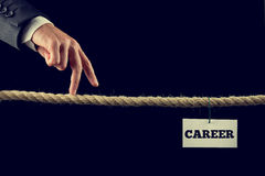 Path to a successful career. Retro instagram style image of a businessman walking his fingers along a length of rope or a tightrope towards his successful career Stock Images