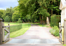 The path to the unknown. Open gates leading to a large looking estate Royalty Free Stock Photography