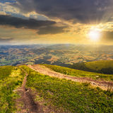 Path to village in mountain valley at sunset. Autumn landscape. path goes ftom the mountain range down to village in valley at the mountain foot at sunset Stock Photo