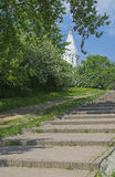 The path to the white stone Orthodox church on a hillside. Royalty Free Stock Image