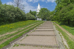 The path to the white stone Orthodox church on a hillside. Stock Photos