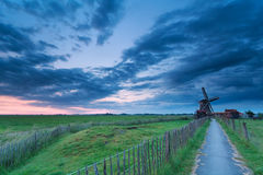 Path to windmill in clouded dusk Royalty Free Stock Image